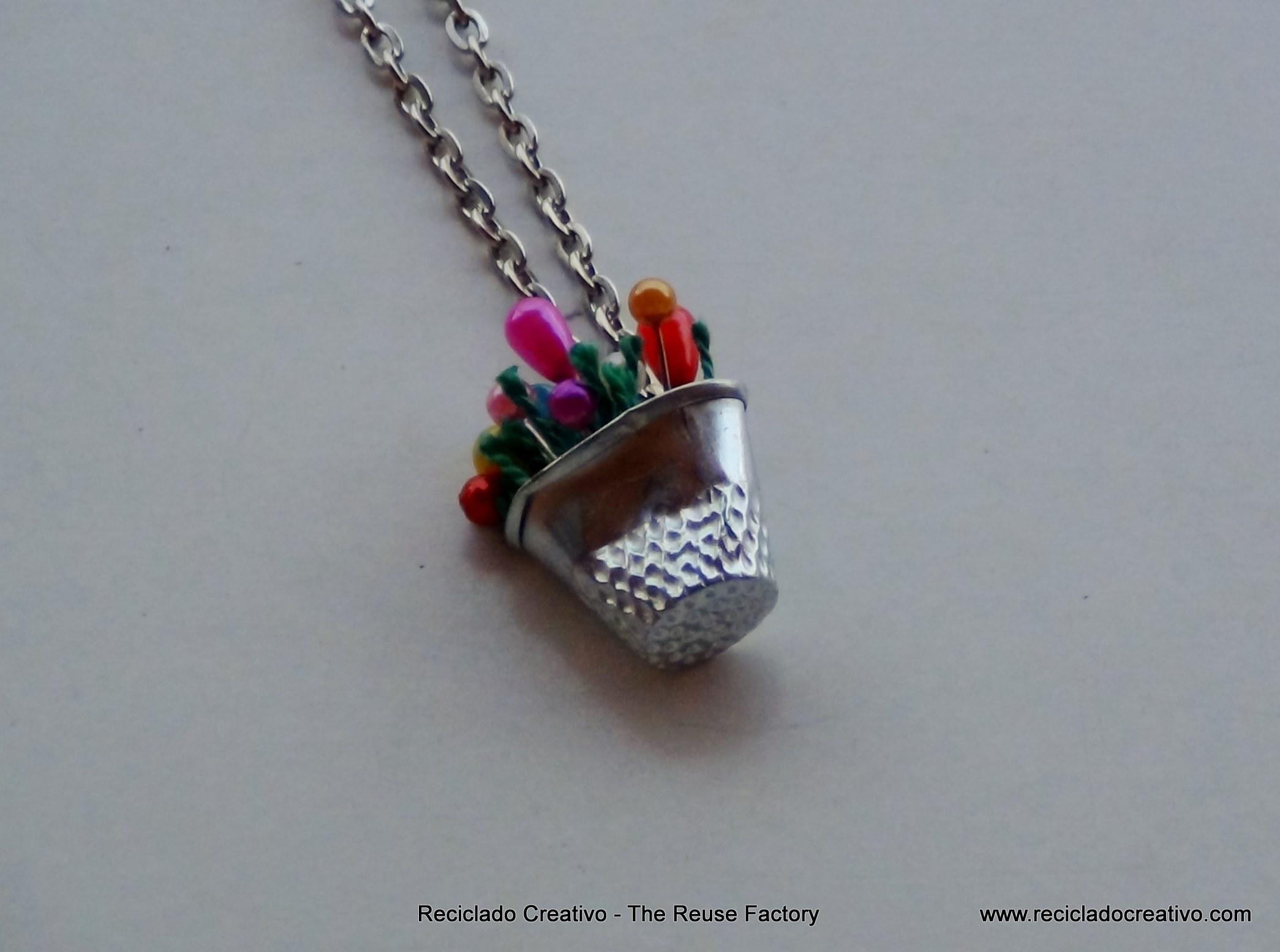 Colgante para collar realizado con un dedal y alfileres de colores