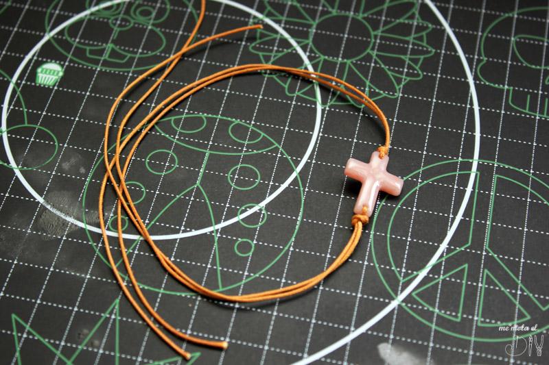Hacer nudo con el cordon de cuero alrededor de la cruz