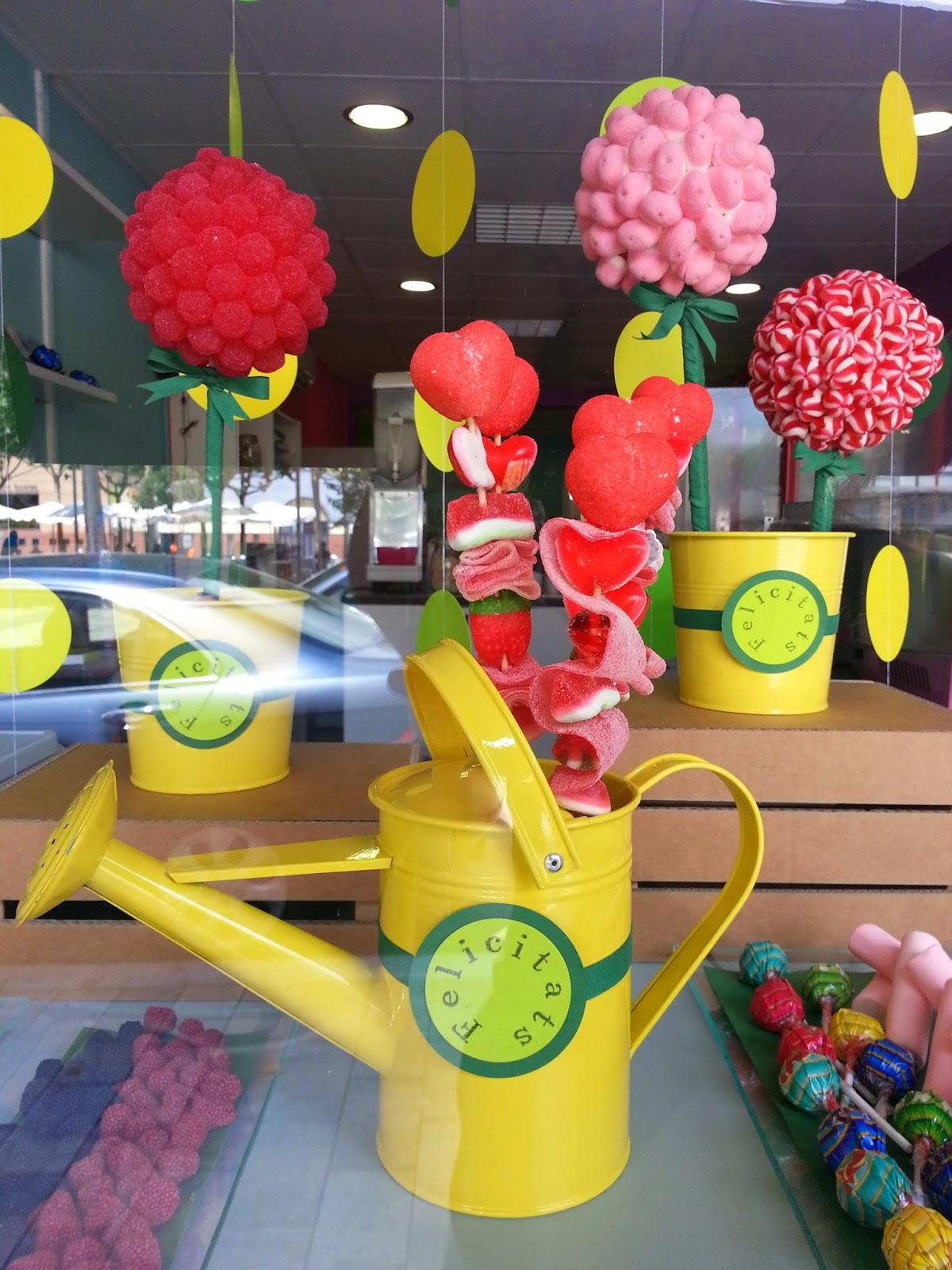 Regadera y macetas con flores de golosinas