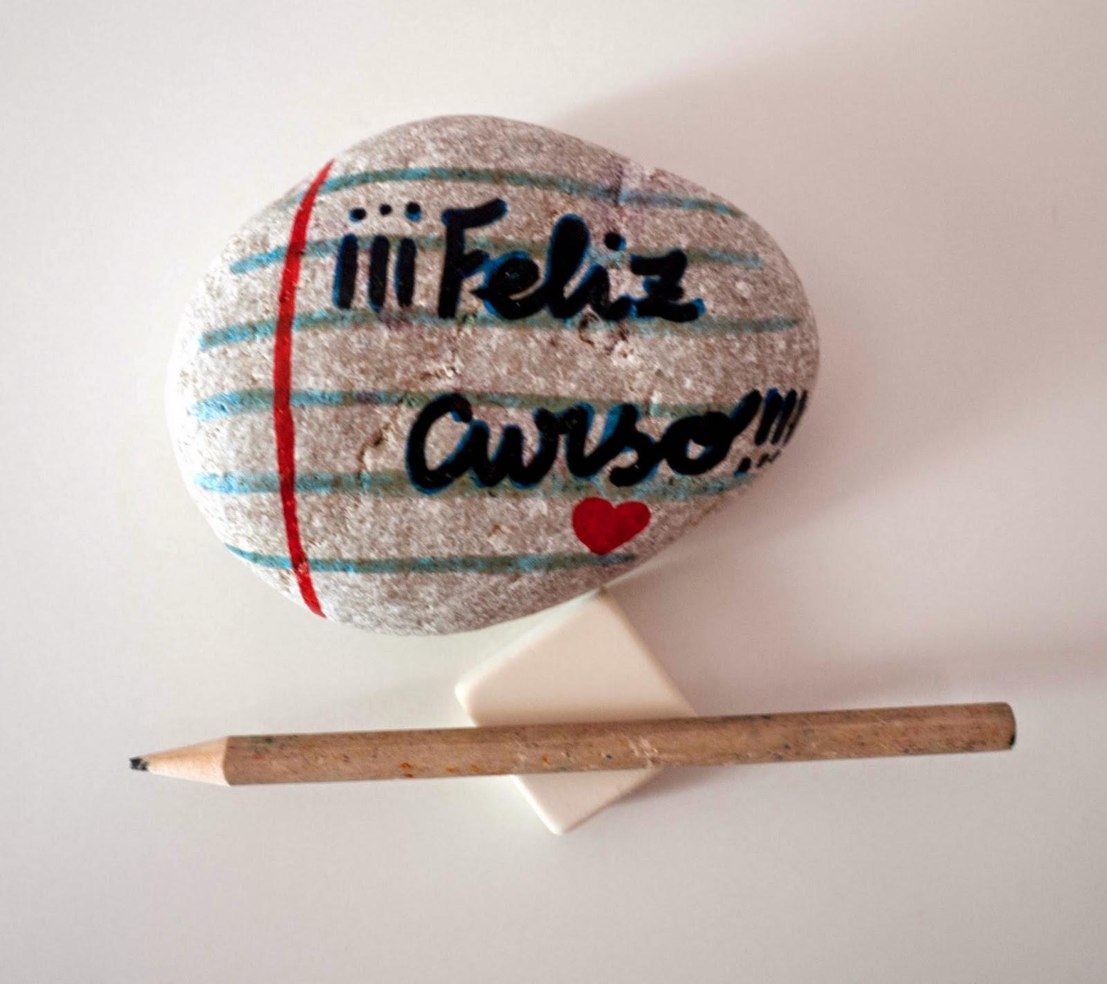 """Piedra con el mensaje """"¡¡¡Feliz curso!!!"""" pintado encima y un corazoncito dibujado en una pauta de hoja escolar."""