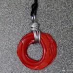 colgante de color rojo con una botella de pllástico