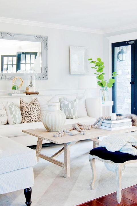 Salon decorado en tonalidades neutras. Detalle con bolas madera encima mesa auxiliar