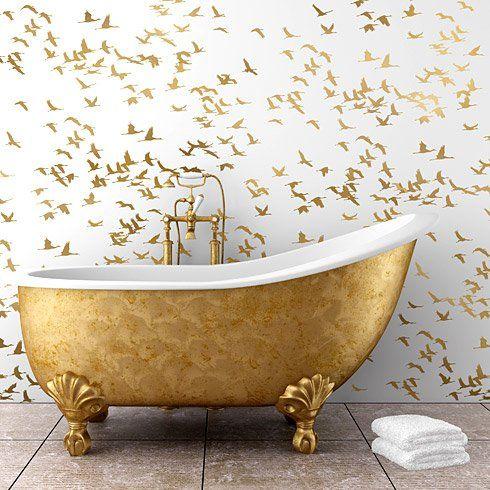 Espacio baño con bañera y papel pared decorado con oro