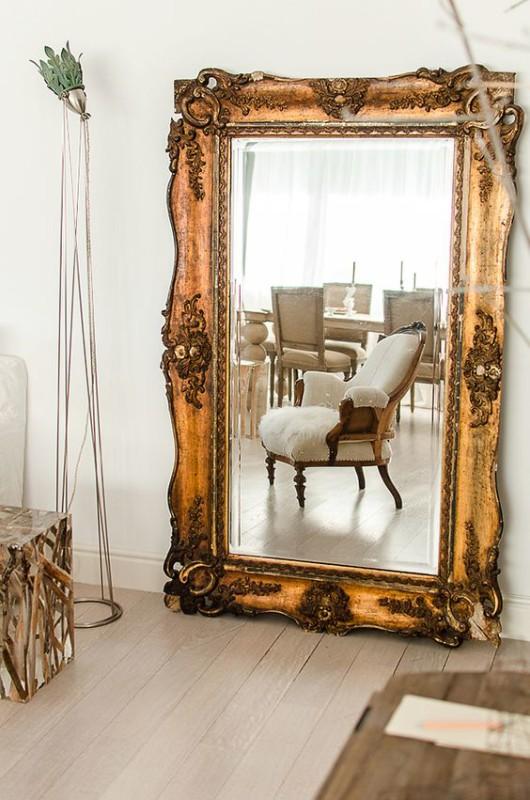 Espacio salón decorado con espejo grande con marco en oro viejo