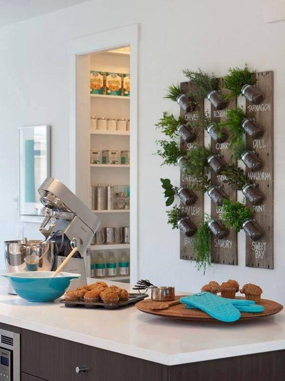 Cocina decorada con una zona verde vertical con plantas aromáticas