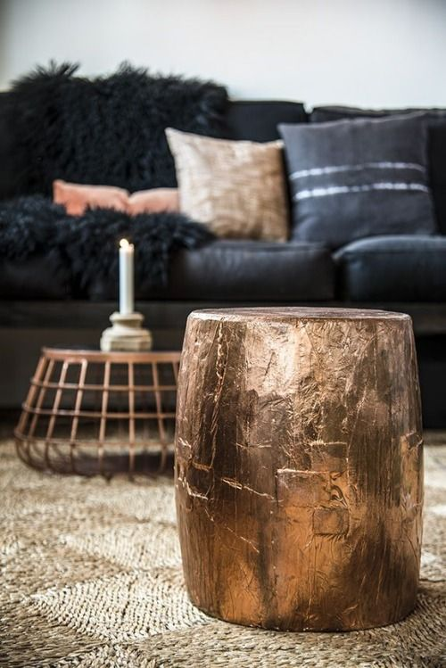 Salón con mesa auxiliar y tronco de madera decorado con pan de oro