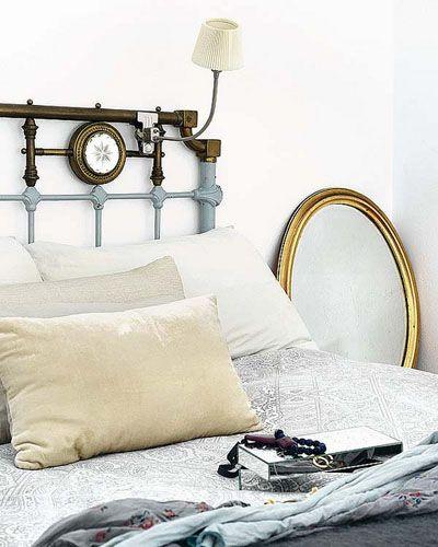 Dormitorio de estilo shabby con espejo con marco en oro