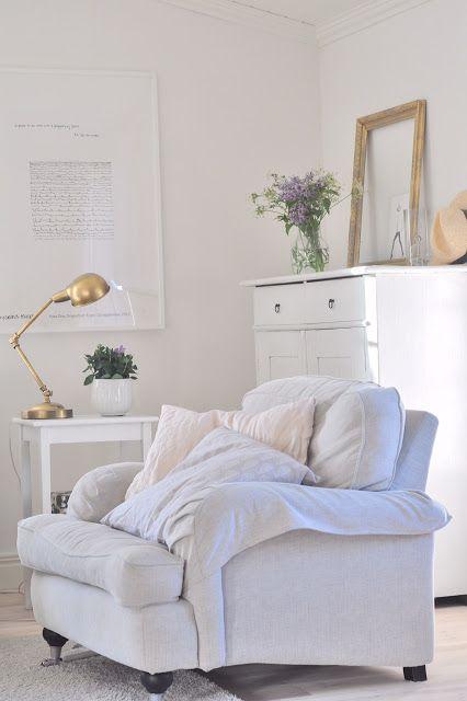 Rincón de lectura decorado en blanco con lámpara dorada