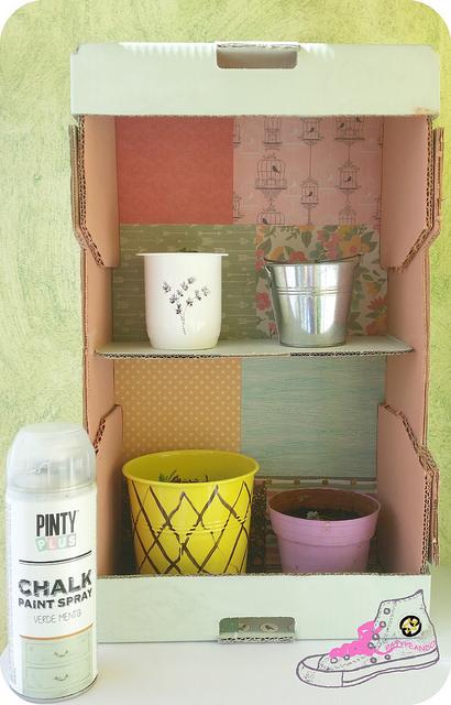 estantería para plantas con caja de naranjas