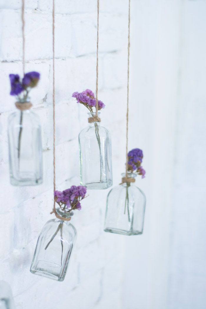 Rama con botellas de cristal y flores