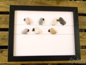 Cuadro de pájaros de piedras sobre cable