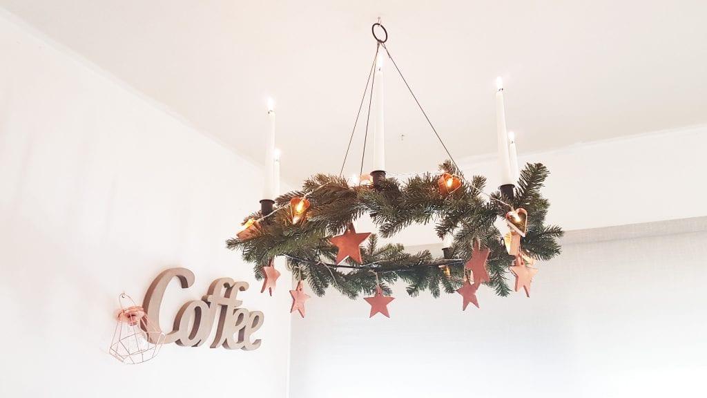 Navidad en cobre - Las estrellas grandes colgadas de un adorno de techo con velas y guirnalda de luces