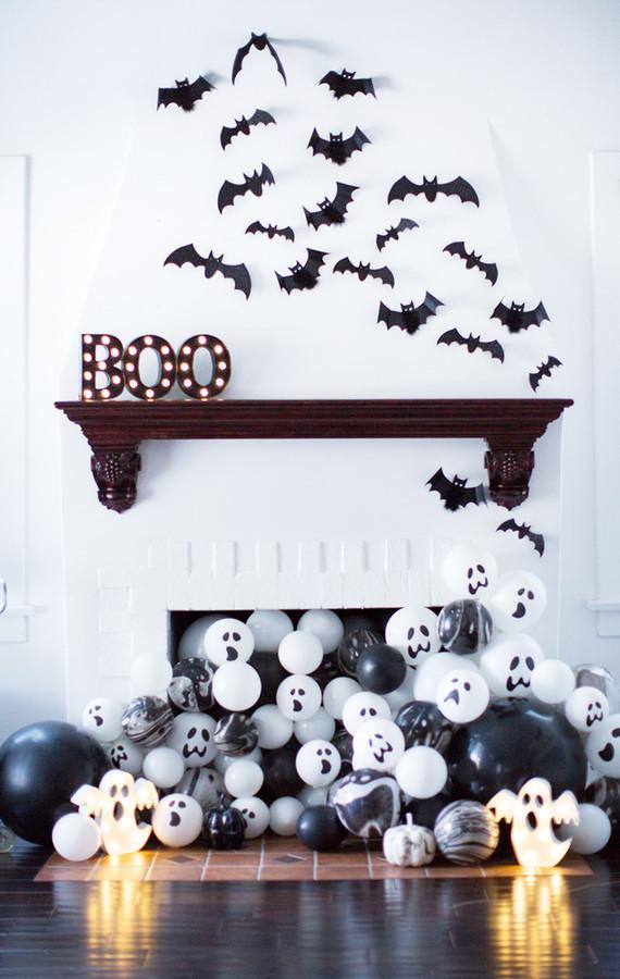 Chimenea decorada para Halloween con murciélagos y globos blancos y negros