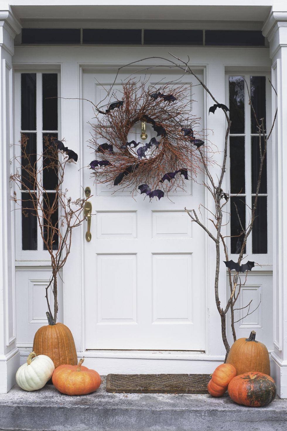 Puerta decorada con corona de halloween, murciélagos y calabazas