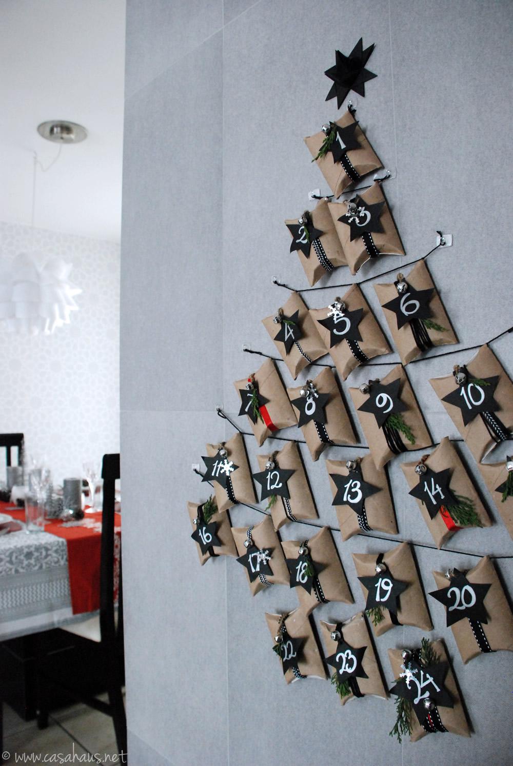 Calendario de adviento hecho con rollos de papel sanitario, sobre la pared