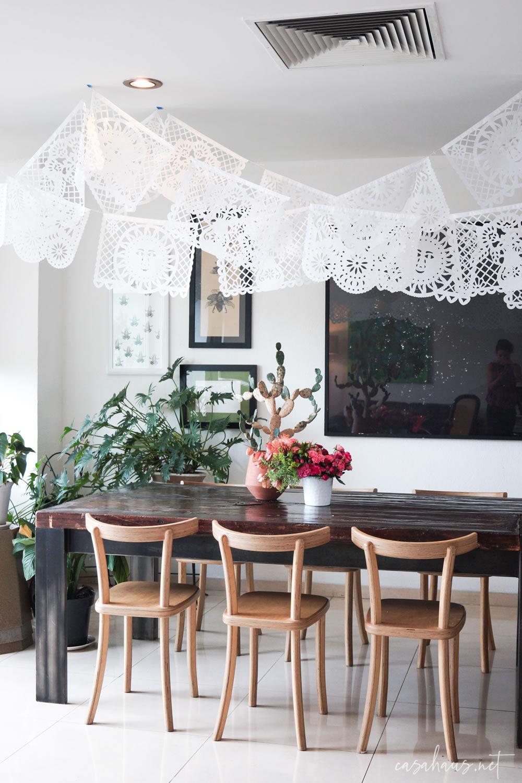 Mesa rústica con papel picado colgado del techo