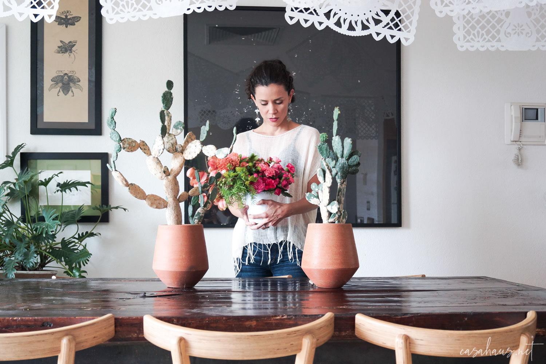 Mujer joven poniendo flores sobre la mesa con nopales