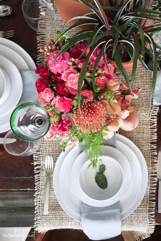 Platos puestos con nopalito, en mesa con cactus y flores rosas