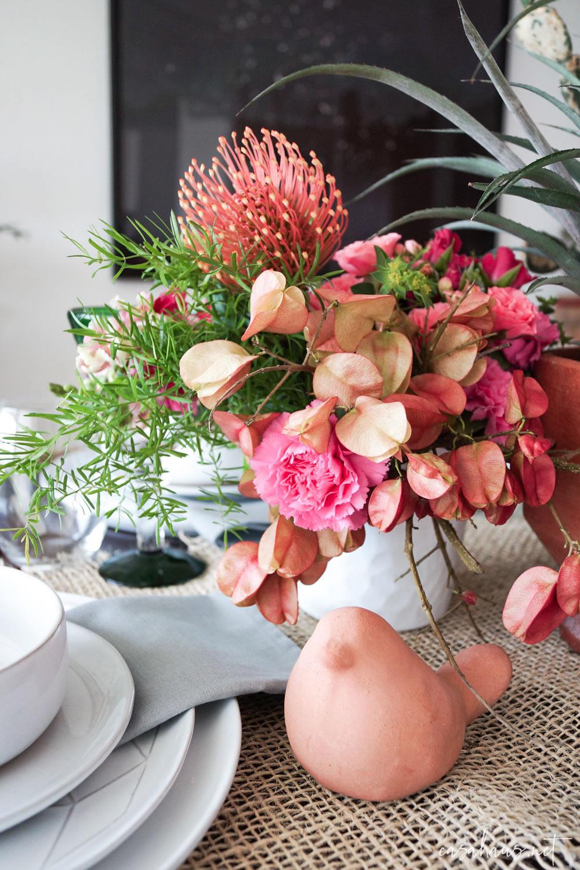 Arreglo de flores rosas sobre mesa mexicana
