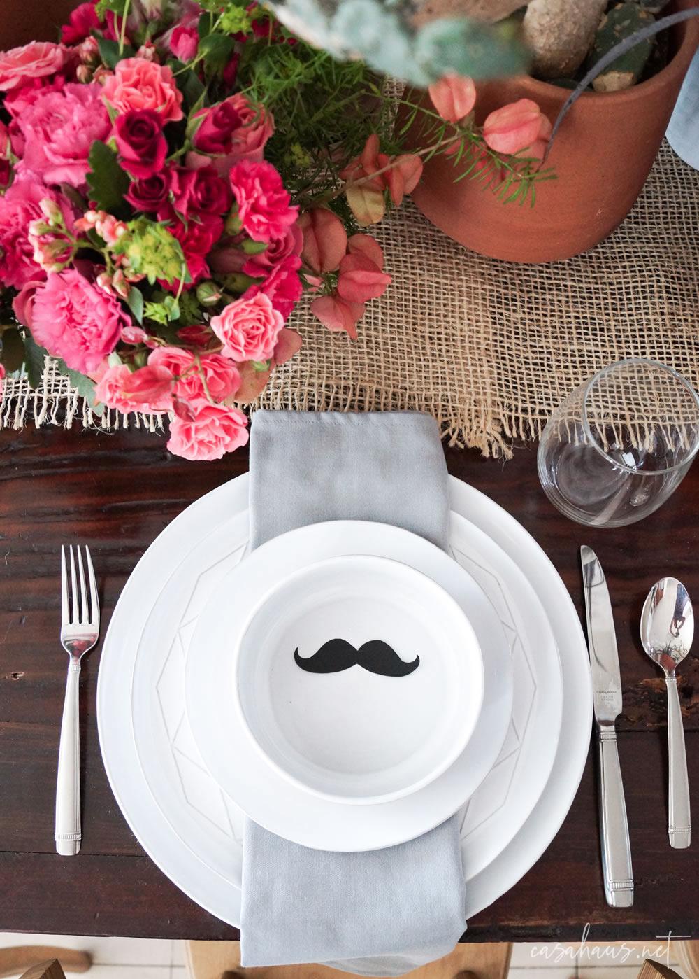 Platos puestos con bigote de papel, en mesa con cactus y flores rosas