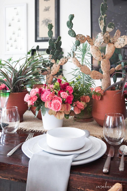Platos puestos en mesa con cactus y flores rosas