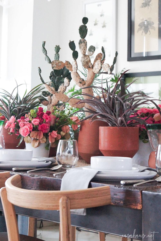 Detalle de mesa con macetas con nopales, bromelias y flores rosas