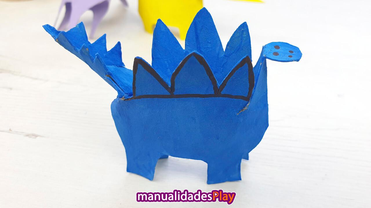 Stegosaurio reciclando rollo de papel