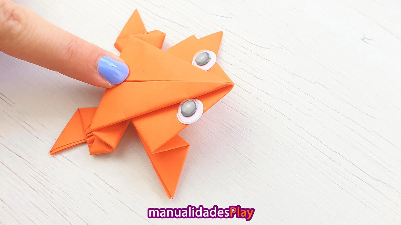 Rana de papel de color naranja preparada para dar un salto