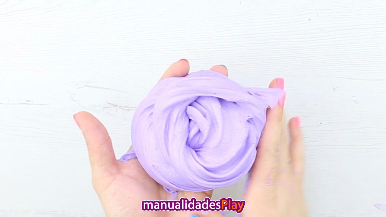 Slime esponjoso de color morado amasado por dos manos