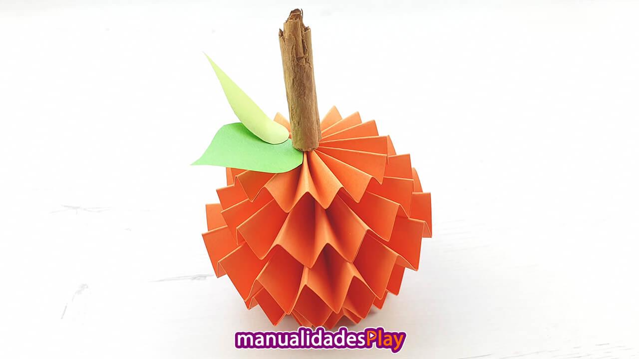 Manualidad de calabaza realizada con hojas de papel de color naranja