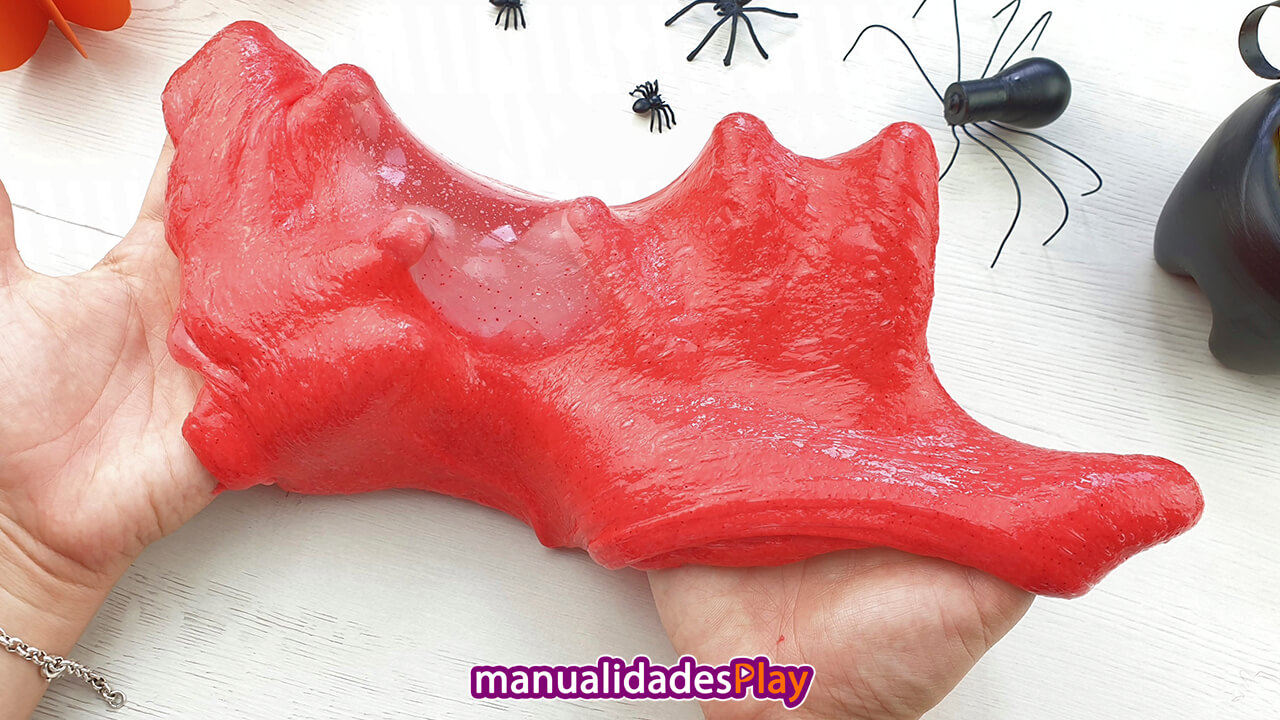 Masa viscosa de color rojo entre las manos que parece un moco sangriento