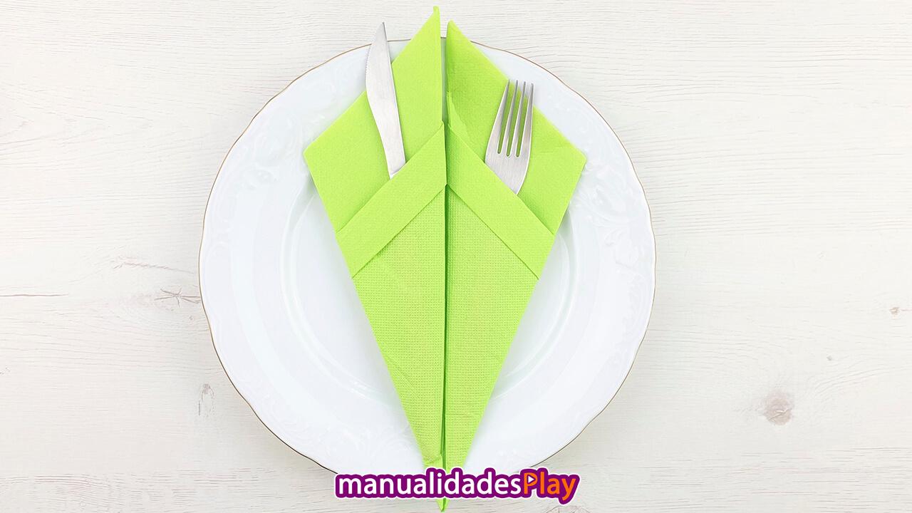 servilleta de color verde doblada en forma de cono con cubiertos dentro