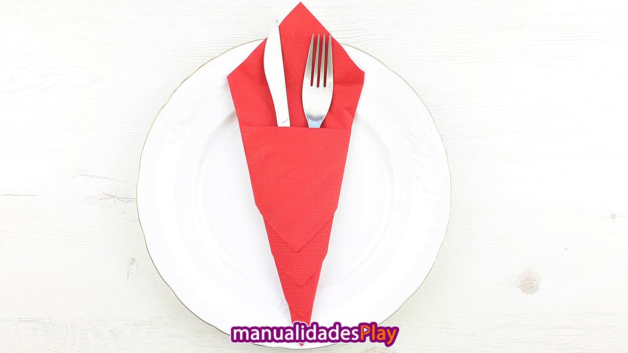 Servilleta de papel roja doblada en forma de cono doblada como portacubiertos