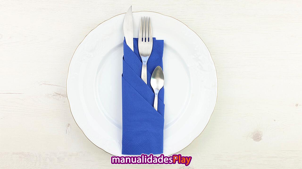 Servilleta de color azul doblada de forma elegante con cuchillo, tenedor y cuchara en su interior