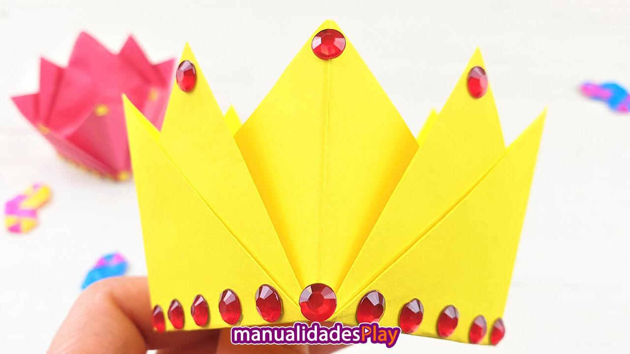 Corona de origami hecha con papel amarillo y perlas