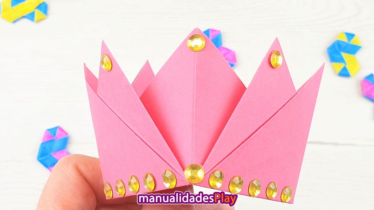 Corona de papel de color rosa con perlas