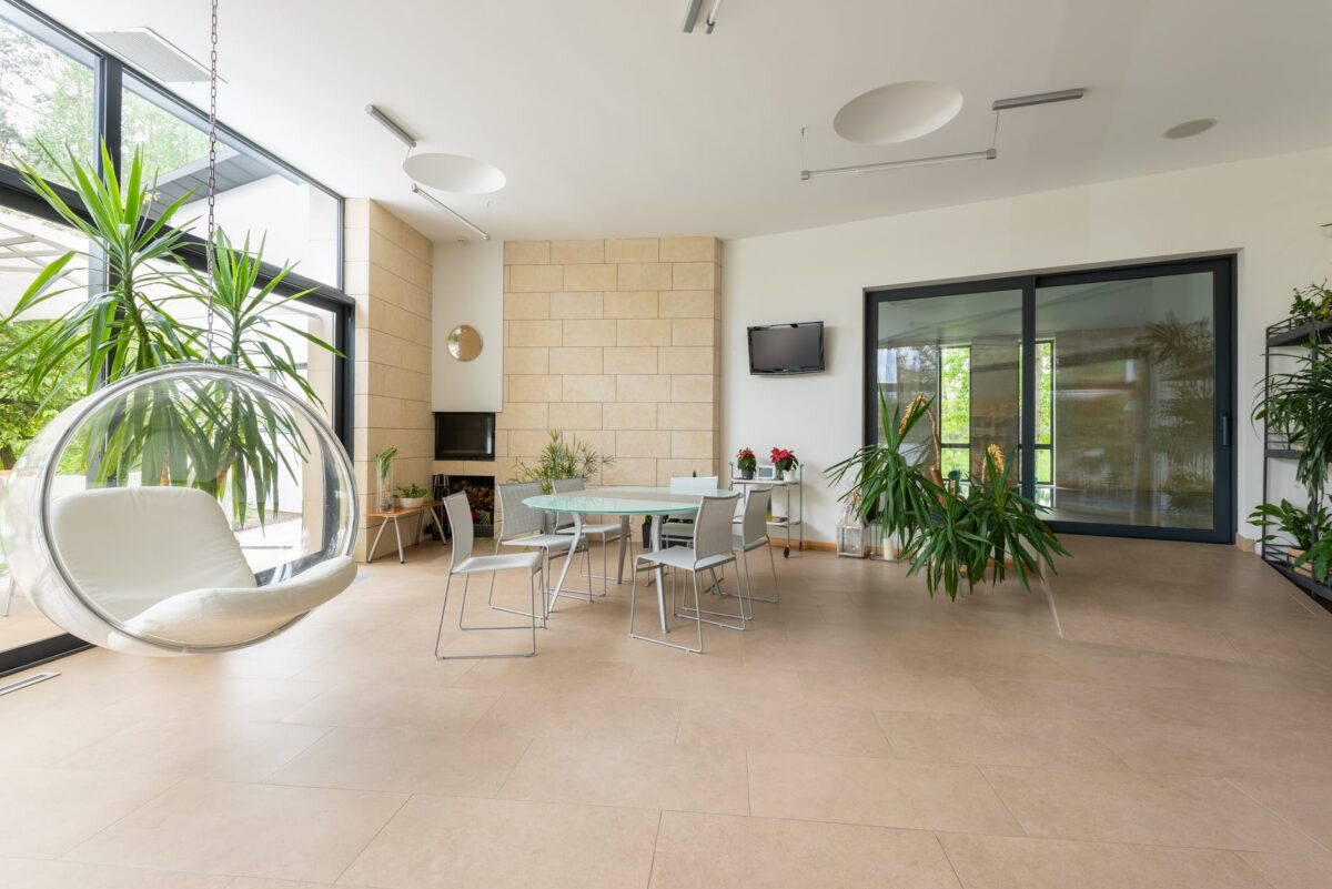 interior of spacious apartment with bubble chair and green plants