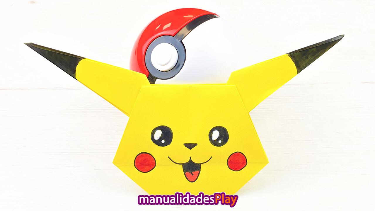 Cara de pikachu de origami realizada con papel de color amarillo y una pokeball detrás