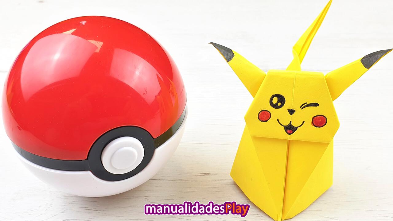 Pikachu de origami en tres dimensiones guiñando un ojo al lado de una pokeball